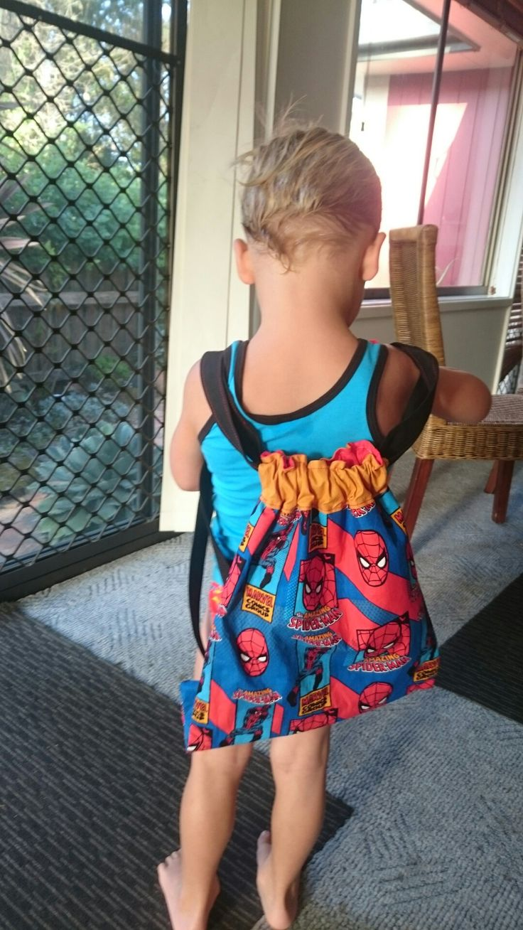 """Drawstring backpack for Lucas. Spider man novelty print. Approximately 12"""" by 17"""". Red lining. Mustard contrast fabric. Black straps. Fabric for straps cut at 4 1/2"""" folded to centre twice then top stitched in contrasting red thread."""