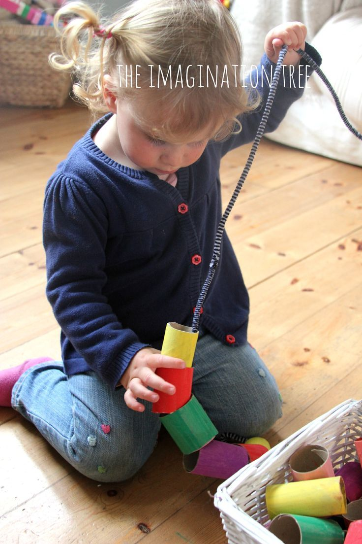Toddler threading activity with giant cardboard beads. Could be a little project to have them paint the tubes, let them dry, and cut the tubes into smaller lengths (with some help).  Add stickers for decoration and even more fine motor practice!