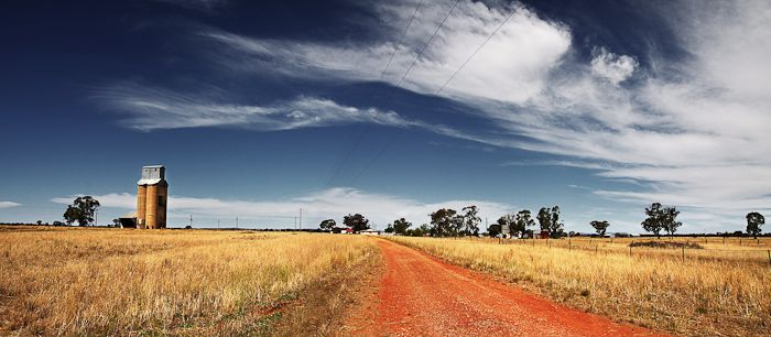 Nelungaloo Road  Nelungaloo, NSW Australia    A dirt road resides along the edge of the railway leading towards someones farmstead and grain silos.