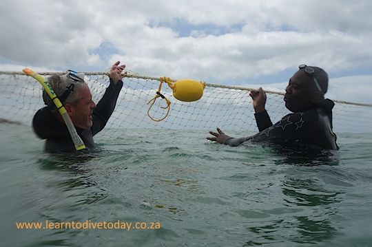 Murray and Monwa discuss the shark exclusion net at Fish Hoek Beach, Cape Town