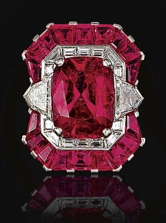 PINK SAPPHIRE AND DIAMOND RING, OSCAR HEYMAN & BROTHERS.  Set at the centre with a cushion-shaped pink sapphire between shield-shaped diamonds, within a border of square-, calibré-cut and baguette diamonds, further decorated with similarly cut pink sapphires, the shoulders set with tapered baguette and baguette diamonds, mounted in platinum,  numbered