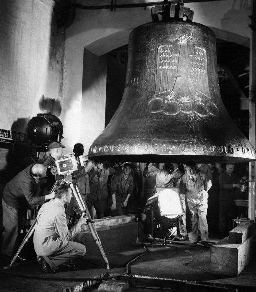 """Die in Bochum gegossene, mehr als vier Meter hohe Olympia-Glocke wurde in einem """"Triumphzug"""" nach Berlin überführt und am 11. Mai 1936 in den Glockenturm am Stadion gehoben. Sie wurde zum Symbol für die Spiele und für ein """"wiedererstarktes Reich""""."""