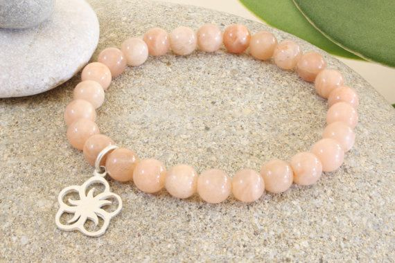 This is a very pretty gemstone bracelet with 6mm sunstone beads and a sterling silver flower charm. Nice to wear in the spring and summer! It lso