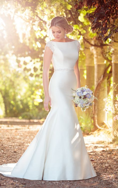 This structured wedding dress from Essense of Australia was made for the bride in search of a classic, timeless style with a touch of glamour. The high neckline of this gown is accented beautifully with Diamante-beaded cap sleeves that coordinate with its detachable Diamante-beaded belt. Visible seaming helps shape this Pearl Mikado gown to the body, helping to show off your curves. The back of this gown features a deep V back, and zips up beneath fabric and Diamante buttons.