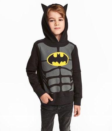 Sort/Batman. En genser i sweatshirtkvalitet med föret hette, trykk foran og vrangbord nederst og på ermene.