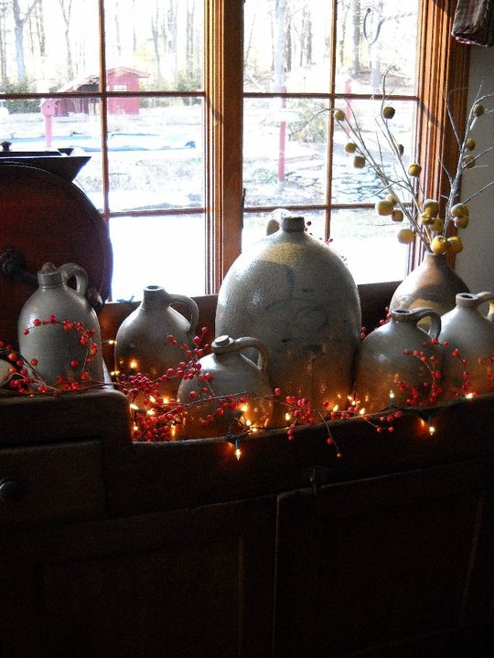 Old Pottery Jugs with orange lights and berries in a dry sink