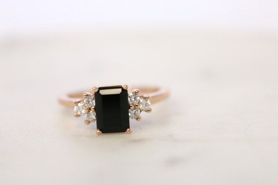 This Onyx dream is a beautiful and edgy engagement ring alternative, or a perfect everyday wear accessory piece. Details  14K Rose Gold (available in yellow and white gold upon request)  Center Stone: 5x7mm Emerald cut black Onyx stone  Diamonds: Six 1.9mm I1, G-H genuine round diamonds  Gold: 14K