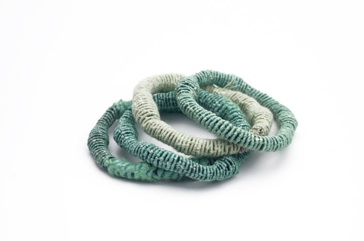 coiling one of a kind bracelets. each piece is handmade, hand dyed.
