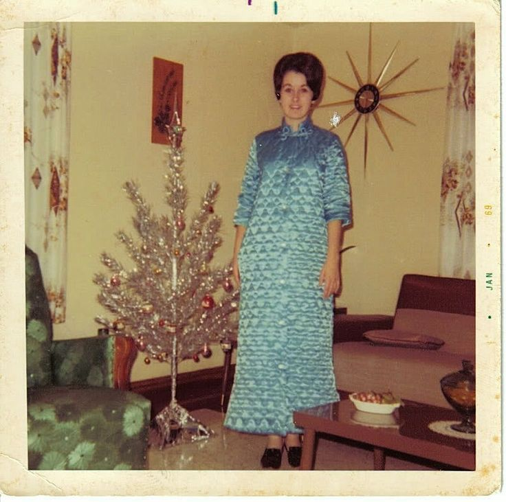 .There is so much about this photo of someone else's mom at christmas that brings back memories: The aluminum tree, the atomic clock and the quilted robe, the fabric and style of couch.........