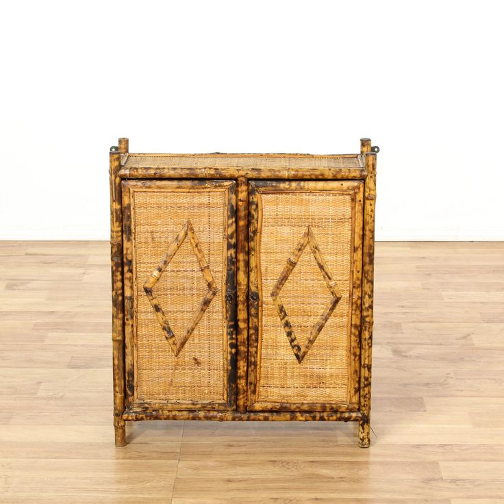 This tropical medicine cabinet is featured in a bamboo with a speckled tortoise shell finish. This bohemian cabinet has 2 woven front diamond doors, a large interior cabinet with shelving and metal wall hanging brackets. Perfect for storing toiletries in a bathroom! #bohemian #storage #cabinet #sandiegovintage #vintagefurniture
