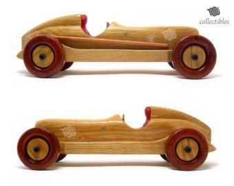 Hermosa brillante bólido inspirada en varios modelos de Ferrari de F1. La pieza tiene un acabado natural y brillante y se verá hermosa en su vitrina, estantería o escritorio! Suave y agradable al tacto. Ruedas se mueven independientemente. Ideal para un regalo importante.   Materiales Abedul multiplex, madera de haya, acabado brillo, pernos,  Dimensiones cm: altezza 6,5 x lunghezza 25 x profondità 10,5 pulgadas: altura 2,6 x longitud profundidad x 9,8 4,1  Escala 1:18  Peso 345 g - 0,8…