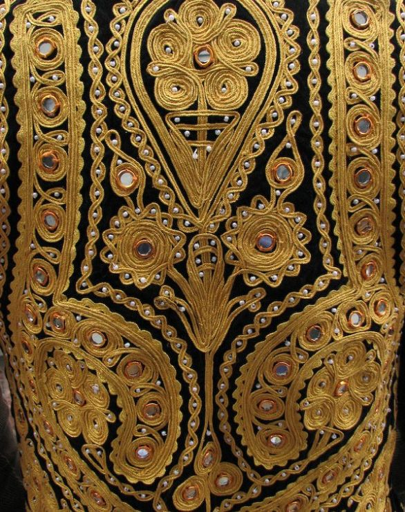 This embroidery or ribbon applique style is called khamak dozi or Zardozi,  extremely intricate and detailed traditional Afghan embroidery.  The picture also shows the traditional sewn on shisha mirrors.