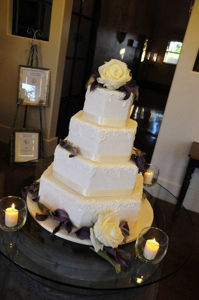 4 tier hexagon covered in ivory fondant with piped grape vine detail around the upper rim of the tier and wrapped with an ivory ribbon. Photo by Shaun Baland, Flowers by Visual Impact.  Wedding Cake