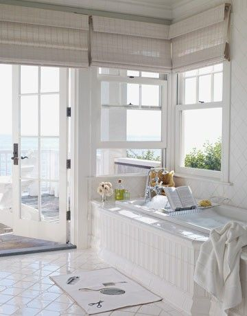 Great example of Woven Wood Roman Shades as an outside mount application in a white bathroom