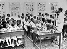 An adult man speaks to several dozen children who are seated on school benches…