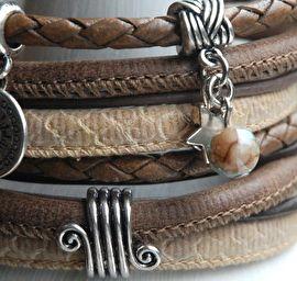 Wikkelarmband met bedelsWikkelarmband in warme bruintinten. De armband sluit door middel van de mooie zilverkleurige sluiting.