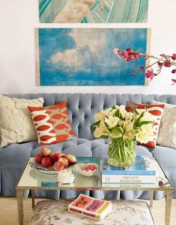 Tufted blue couch (looks vintage) with an assortment of brightly colored pillows fresh flowers and a fabric ottoman. Shabby cottage