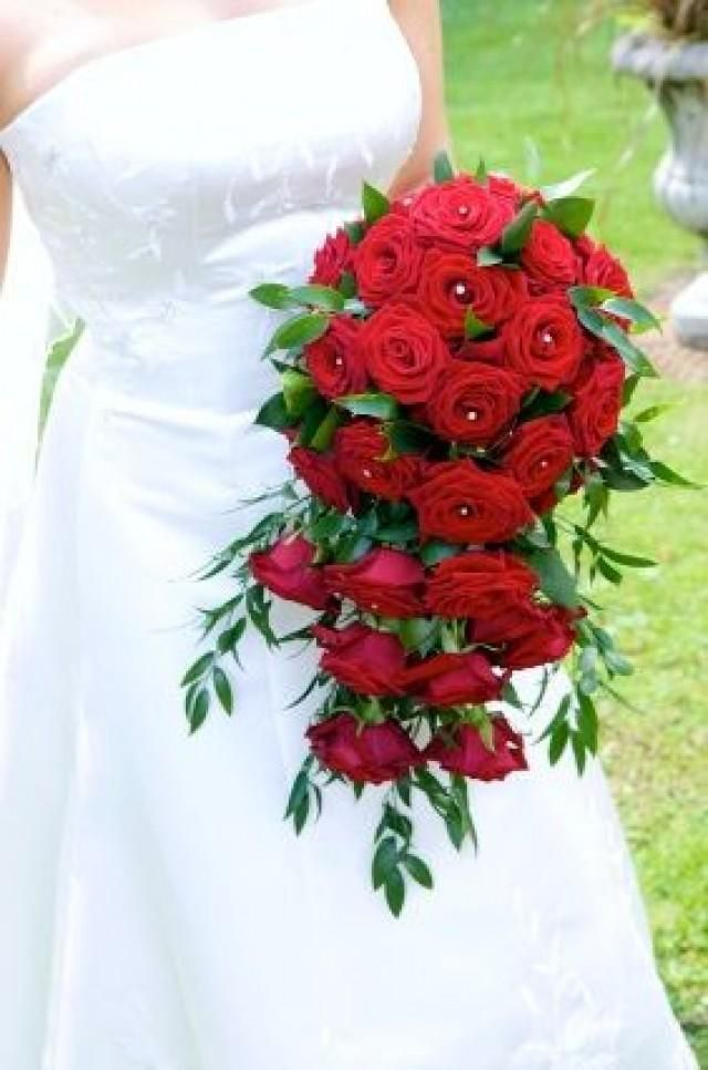 A cascading bouquet of red roses and ruscus leaves. Some rose centers are embellished with rhinestones for that extra sparkle. cascad