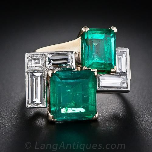 A bright and colorful example of mid-twentieth century wearable sculpture. An artful Mondrian-esque grouping of geometrical shapes rendered in a pair of vibrant green Columbian emeralds: 3.00 carats and 2.00 carats; and five bright-white baguette diamonds, together weighing 1.75 carats. This unique and artistic vintage gemstone ring measures 13/16 inch side to side by 11/16 inch top to bottom. Platinum over yellow gold. Tres cool!