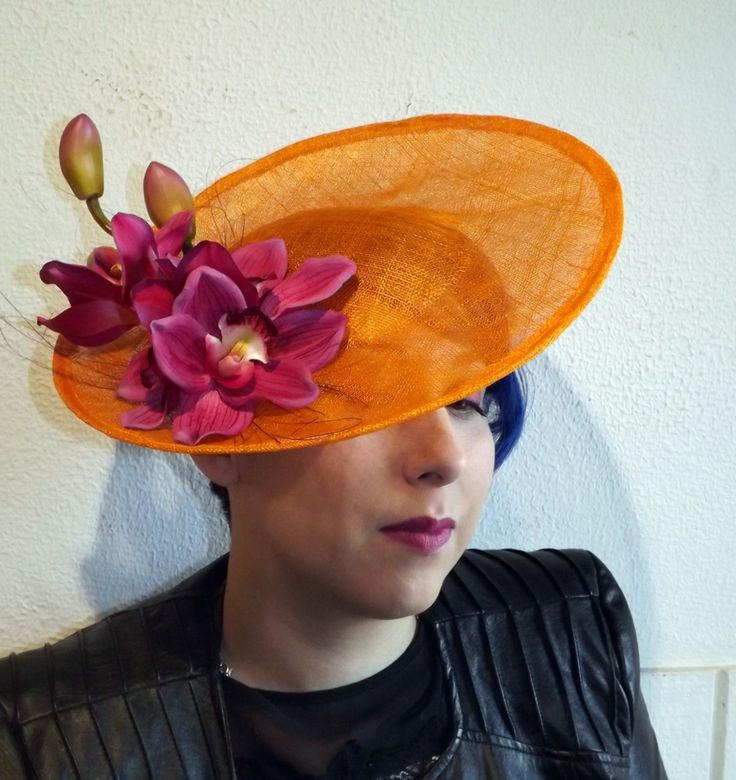 A beautiful hand dyed sinamay saucer is created by using traditional millinery techniques. Once the sinamay was dyed it was pulled and steamed over a wooden hat block to create its shape. Once dry the hat is wired to keep its shape and sewn with yellow and red thread around the edges. Large purple orchids sit happily on the hat with some purple feather fringe poking out.  This hat will definitely have you standing out in the crown and is perfect for any occasion. Hat stays on with a…