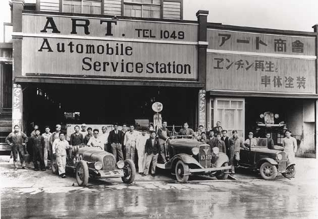 "The Hamamatsu branch of Art Shokai around 1935. The car on the left is ""The Hamamatsu"" and standing beside it with sunglasses is Mr. Honda."