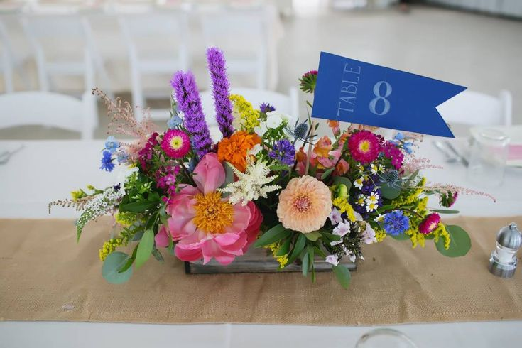 A very colorful centerpiece with a navy pennant flag table number. Rustic burlap runner. Rainbow flowers wedding. Pennant flag table numbers. Real Wedding. Wedding Inspiration. A Heritage Prairie Farm Wedding in Elburn, Illinois. Wedding Venue. Reception. Photo by Hazelton Photography. Flower Centerpieces made by Avant Gardenia.
