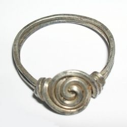 "Anglo-Saxon and Viking (5th-11thC)  ""An Anglo-Saxon period silver finger ring made from a single strand of square-section silver wire. The wire is coiled twice to form the hoop, and the remaining length is used to produce a double-start spiral bezel. The two ends of the wire are wound round the hoop to form shoulders. Traces of gilding are possibly present."""