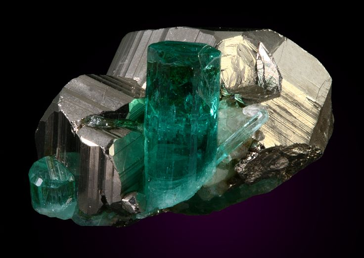 """Beryl (Var: Emerald), Pyrite  Photo Copyright © Dan & Diana Weinrich Minerals  - This image is copyrighted. Unauthorized reproduction prohibited.  Locality: Vasquez-Yacopí Mining District, Boyacá Department, Colombia  A neat combination specimen consisting of a 2.1 x 1.5 x 1.2 cm """"matrix"""" of bright sharply formed pyrite crystals, these hosting a gem quality glassy transparent lustrous terminated emerald crystal measuring 1.0 x 0.4 x 0.4 cm in size."""