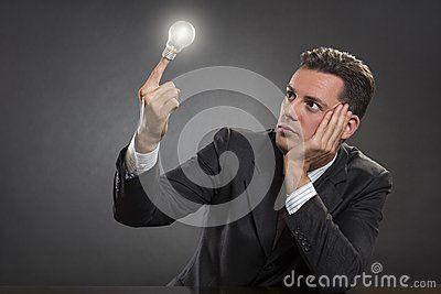 Portrait of handsome pensive entrepreneur looking at glowing bulb and seeking for smart business vision over dark grey background. Think smart to succeed.