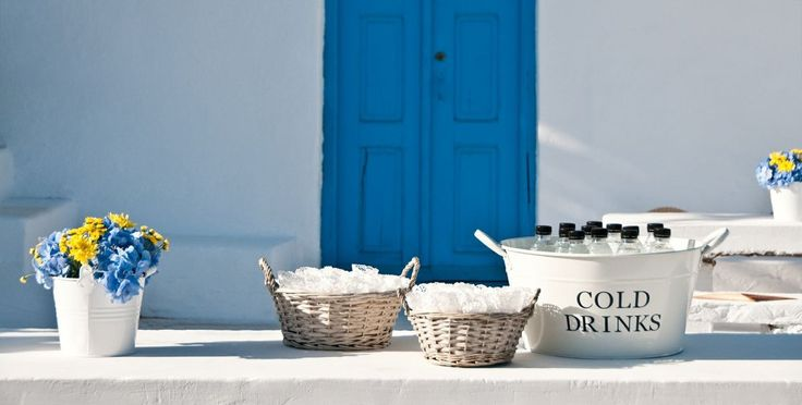 When Brazil Meets Greece Wedding @ Alemagou, Mykonos by De Plan V. Church's refreshment corner for guests. Small bottles with cold water &  baskets with hand made craft parer cones filled with rise for the ceremony. Small white pots with fresh cut flowers in mediterranean colours.