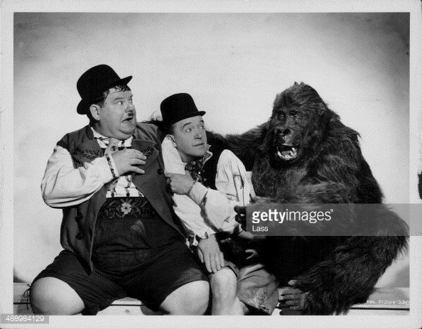 Comedy double act Oliver Hardy and Stan Laurel, posing with a man in a gorilla suit in a promotional portrait for the movie 'Swiss Miss', 1938.