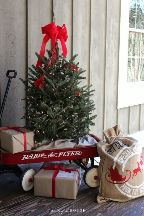 A classic little tree displayed in a vintage red wagon (next to Santa's burlap sack!) makes for a charming front porch display.  Get the tutorial at Talk of the House.