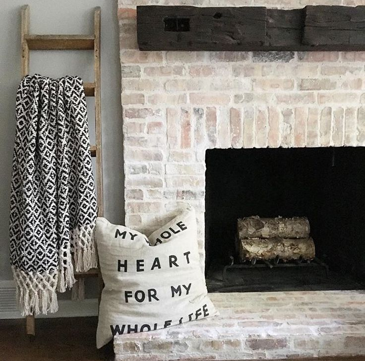 Whitewashed old Chicago brick fireplace and reclaimed wood mantle
