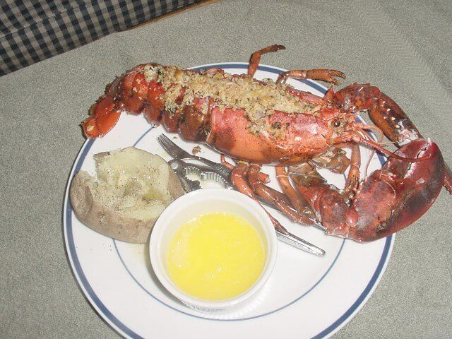 A recipe for Baked Stuffed Lobster made with live Maine lobsters, unsalted butter, onion, Italian parsley, raw shrimp, salt and