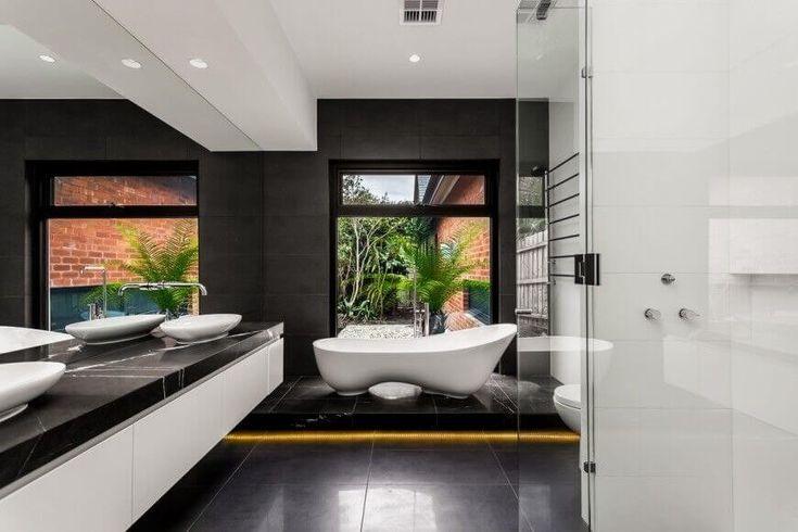 Die freistehende Badewanne neben einem offenen Fenster ist ganz trendy suchen, während die gleichen Fett schwarze Farbe als Boden und Wände der dunklen Marmor Eitelkeit Zähler nach oben zeigt.