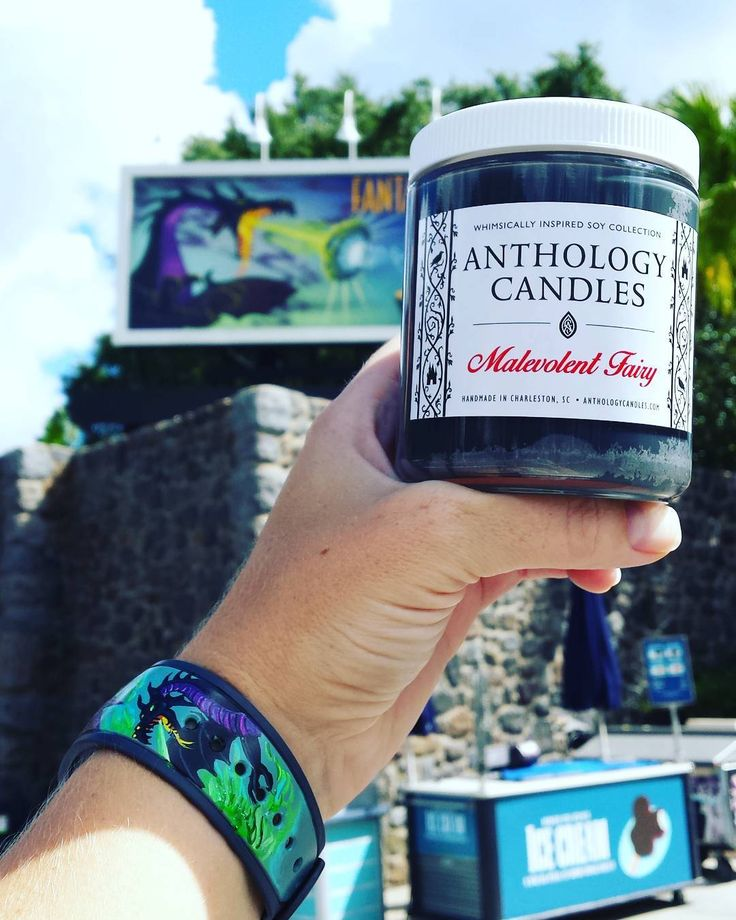 While we were in Disney's Hollywood Studios the other day I was so excited to snag this shot of our Malevolent Fairy from our Villains Collection in front of Maleficent's dragon billboard (from Fantasmic!) that matches PERFECTLY with my Maleficent Dragon Magic Band from @theenchantedbrush  Nailed it again Angi!  Malevolent Fairy is the candle embodiment of Maleficent: Sweet and earthy oak trees and thorny briars dragon essence and fire!And can we please appreciate the incredible label from…