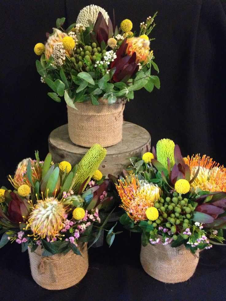 bush blooms table centre arrangements in hessian covered glass vases
