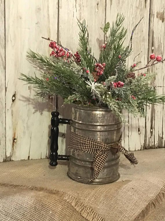 An antique flour sifter brimming over with winter pine greenery, red berries, pine cones and black sparkle spikes. The sifter has a black and tan small check fabric tied around it with a rustic bell in the middle to finish it off. This arrangement can be displayed in any room of