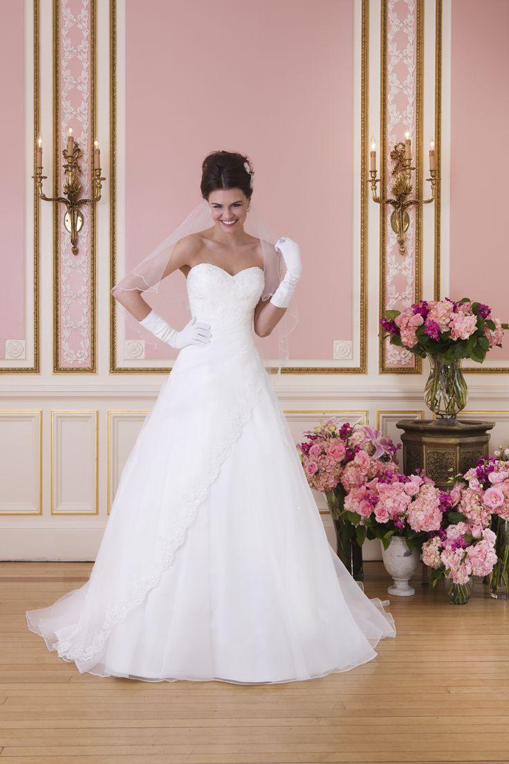 Een A lijn jurk met een sweetheart halslijn van organza met geborduurde kanten applicaties ophet asymmetrische geplooid lijfje en..
