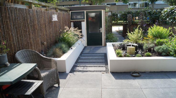 Strakke moderne tuin met wit gestucte verhoogde borders. Foto en ontwerp: Vicas Tuinontwerpen www.vicas.nl.