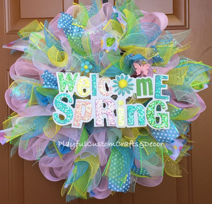 Welcome Spring Wreath would look charming on your front door to welcome in spring. This wreath is made with pastel mesh, Easter egg ribbon, blue polka dot ribbon, and has a Welcome Spring sparkling si