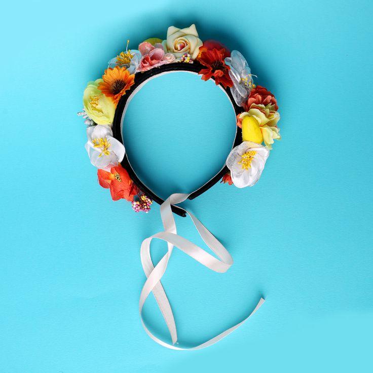 Coroniță din flori – plastic, hârtie, textil  Asamblare manuală pe cordeluță neagră de plastic, imbracata in catifea neagră cu panglică prelungită  Mărime universală  Culori: galben, portocaliu etc.  Flori: diverse