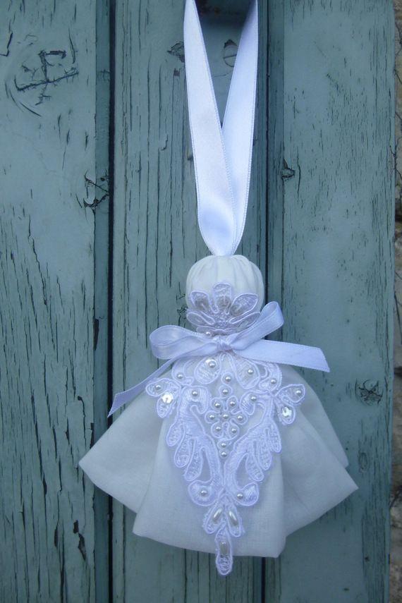 Pompon de porte ou de clé fait d'un jupon de voile de coton et d'un motif de guipure perlée. Il mesure 12 cm (sans le ruban de satin blanc).