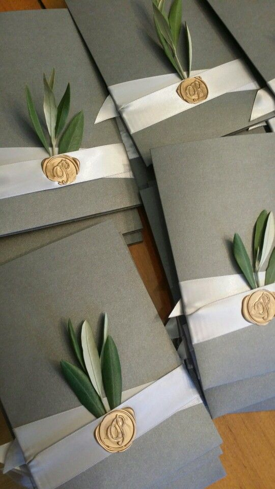 Gorgeous wedding invitations with real olive leaves, satin ribbon, and then sealed with the couple\'s last name initial in gold wax.