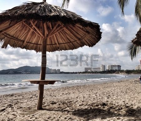 Beach scene with handmade sun hut and cloudy sky. Playa de Ixtapa, Zihuatanejo con palapa