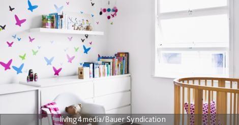 Der dunkle Holzboden und das dazu passende Babybett setzen warme Kontraste zu den weißen Kommoden und der weißen Wand. Zudem wird das Babyzimmer mit kleinen Schmetterlingen in Rosa Blau und Grün gestaltet, die eine liebevolle Wandgestaltung schaffen. Die Schmetterlinge bringen Farbe in den Raum und lassen die Wände lebendig erscheinen.
