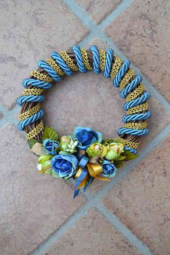 SMALL SIZED WREATH – Avion Blue - PatriziaB.com  Woven from wicker, handcrafted wreath embellished with silk cordon spirals and a refined decoration of rosettes, berries and satin ribbons