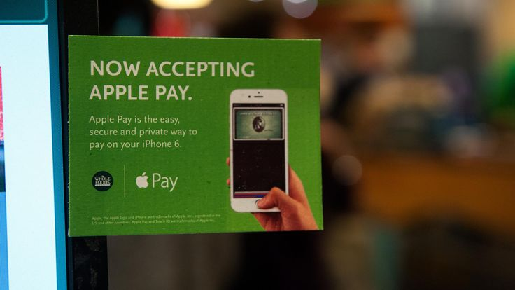 Apple Pay is promoted on signs placed at the cash register of a Whole Foods supermarket in New York.