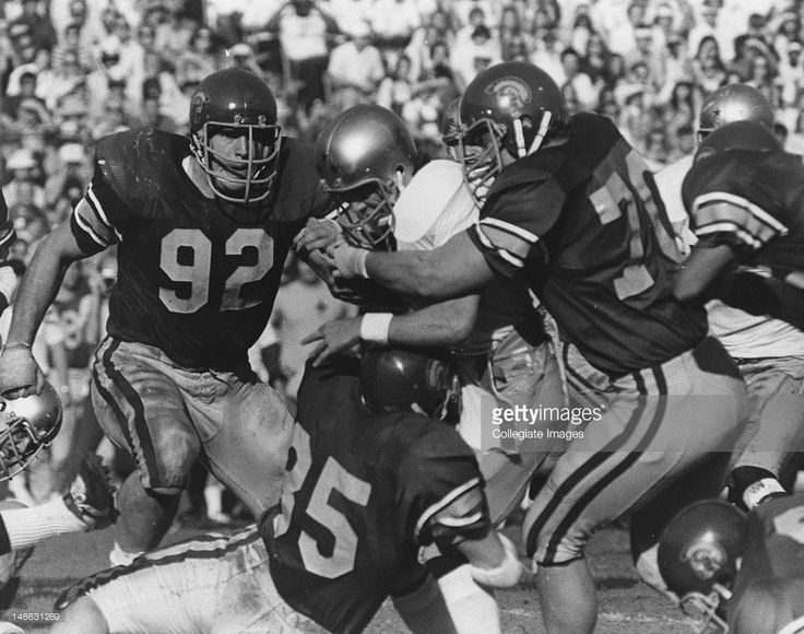 Players of the University of Southern California Trojans football team tackle the ball carrier during the game against the University of Notre Dame Fighting Irish at the Los Angeles Memorial Coliseum in Los Angeles, California.