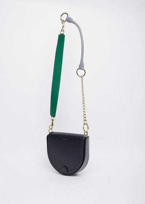 Navy leather satchel bag with an assortment of handles, consisting of gold-hued chains, a removable green wide leather handle and a grey rolled handle, all connected with golden-hued ringlets. Can be